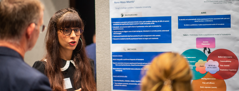 PhD student explaining her research poster to two people at event