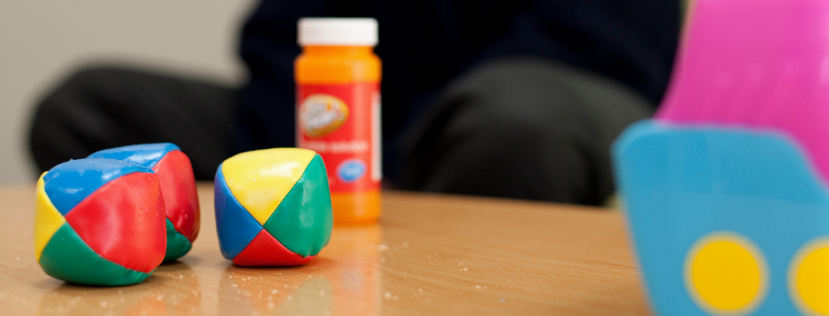 Orange bottle and muticoloured balls on a table