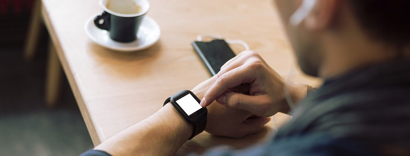 Person checking smart watch at table